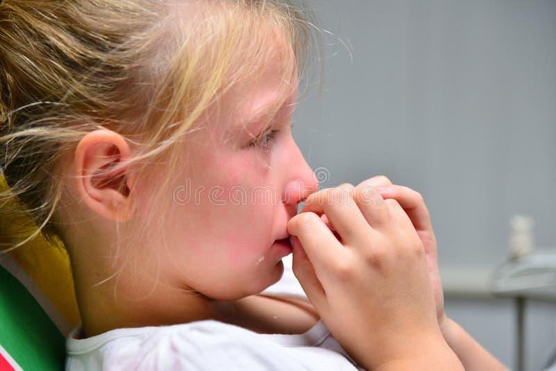 Une petite fille au dentiste pleure avec des larmes à un rendez-vous du ` s de docteur tout en traitant une dent photographie stock libre de droits