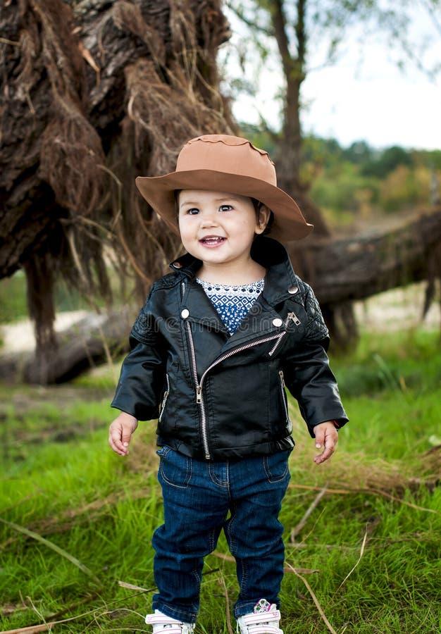 Une petite fille aux yeux bruns de sourire utilise un chapeau de cowboy, un cuir j photos libres de droits