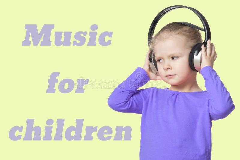 Une petite fille avec des écouteurs écoutant la musique isolat La musique d'inscription pour des enfants photo libre de droits
