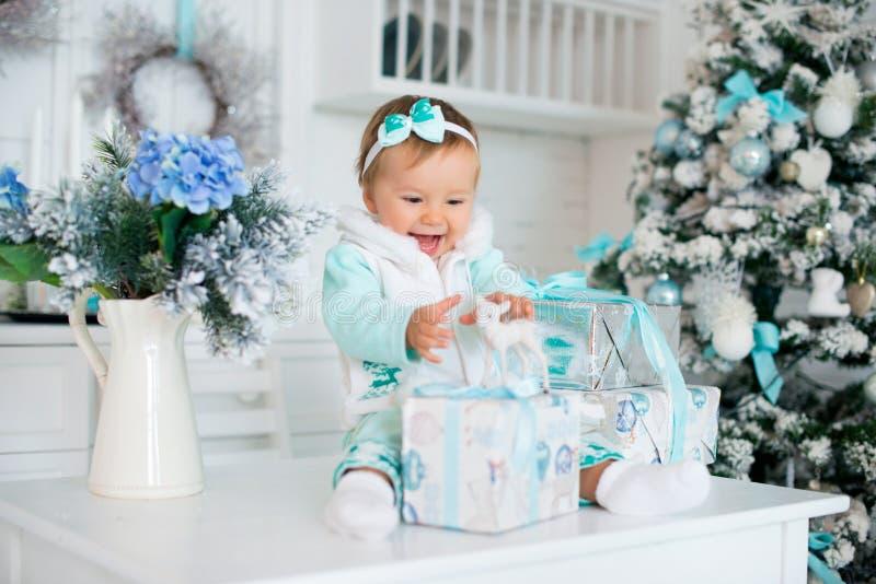 Une petite fille avec des cadeaux et un cerf commun de jouet Vacances de Noël photo stock
