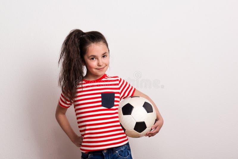 Une petite fille avec du ballon de football et le T-shirt rayé se tenant dans un studio photos libres de droits