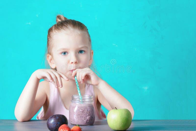 Une petite fille avec les cheveux blonds boit un cocktail sain par une paille Boisson de fruit de Vegan photo libre de droits