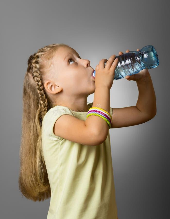 Une petite fille avec les longs cheveux, eau potable de bouteille en plastique sur le gris photos stock