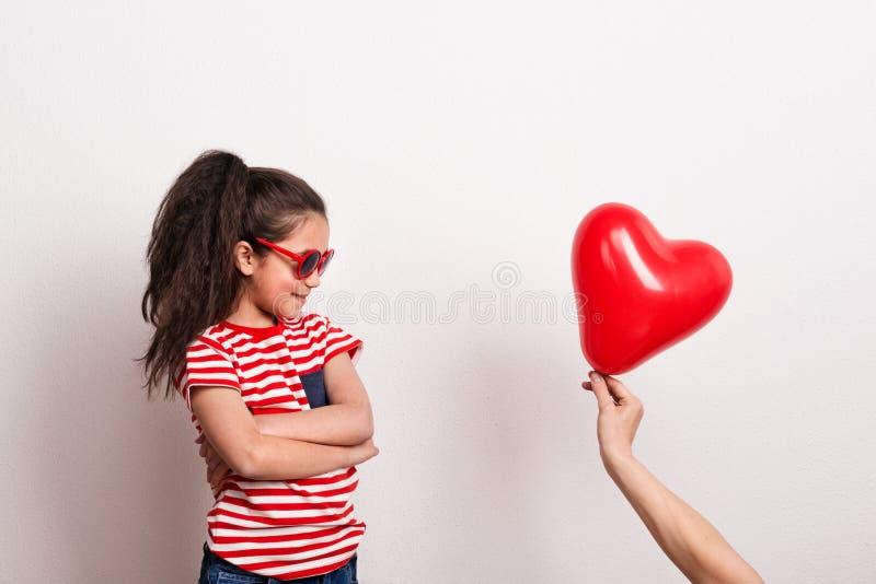 Une petite fille avec les lunettes de soleil rouges et le T-shirt rayé regardant le coeur rouge montent en ballon image libre de droits