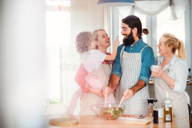 Une petite fille avec les parents et la grand-m?re ? la maison, pr?parant la salade v?g?tale photo stock
