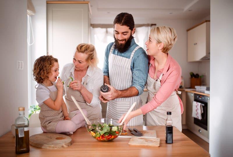 Une petite fille avec les parents et la grand-m?re ? la maison, pr?parant la salade v?g?tale images libres de droits
