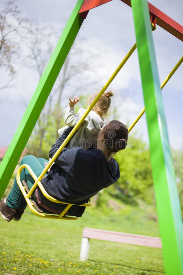Une petite fille avec sa m?re dans le tour de parc sur une oscillation et avoir un bon week-end concept d'un enfant heureux d'enf images stock