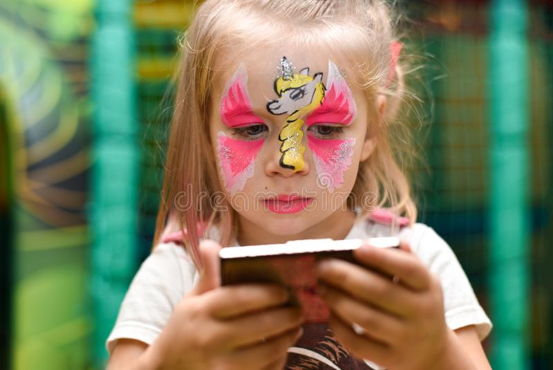 Une petite fille avec un modèle d'une licorne sur ses regards de visage dans le miroir images libres de droits