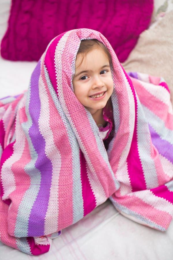 Une petite fille avec une couverture dans le lit image libre de droits