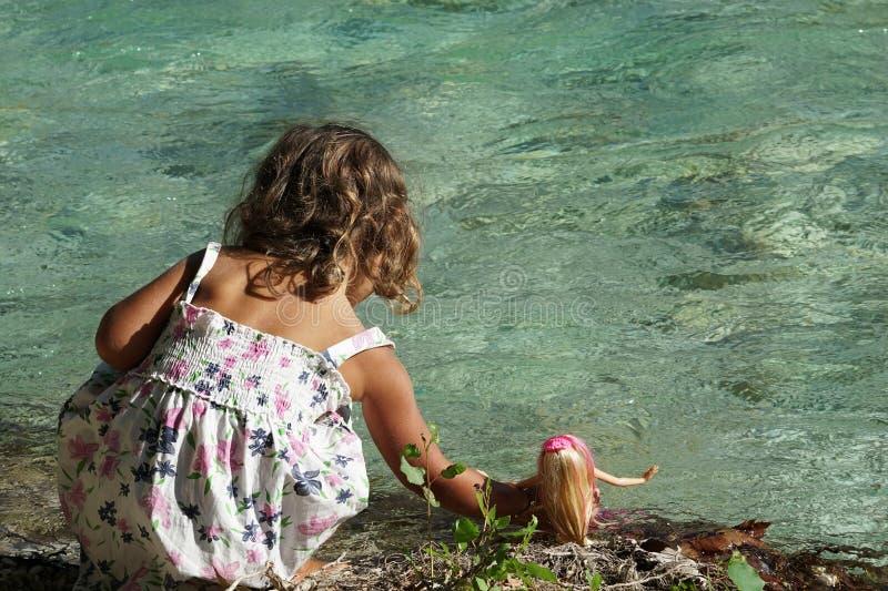 Une petite fille baigne sa poupée en rivière d'Acheron avec sa nature transparente dans Épire, Grèce photographie stock libre de droits