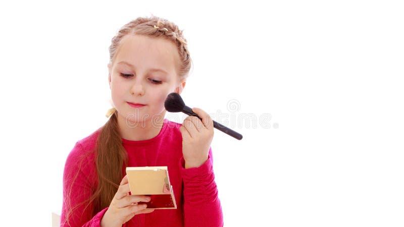 Une petite fille branchée utilise les cosmétiques de sa mère photographie stock