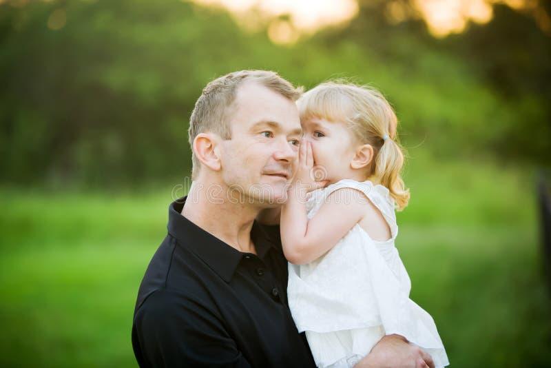 Une petite fille chuchotant un secret à son papa photographie stock libre de droits