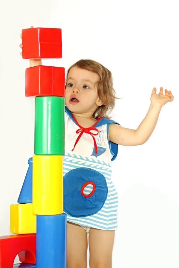 Une petite fille construit une maison. photographie stock