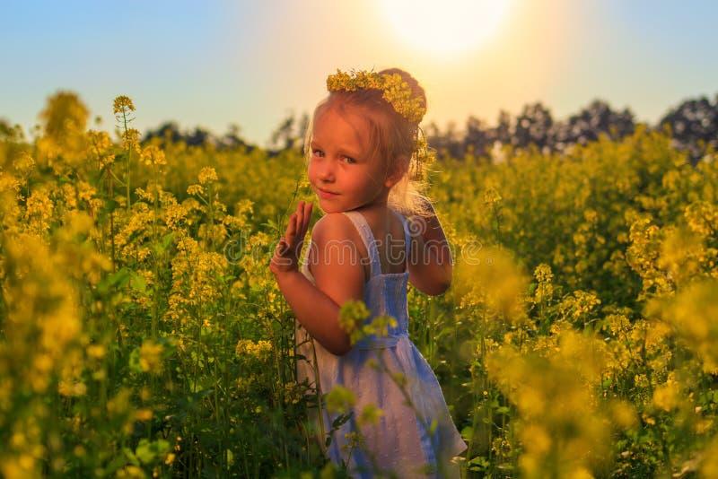 Une petite fille court par un champ de viol images stock