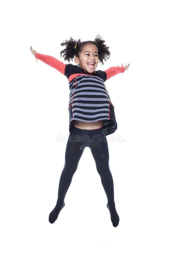 Une petite fille d'afro-américain mignon sautent d'isolement images libres de droits