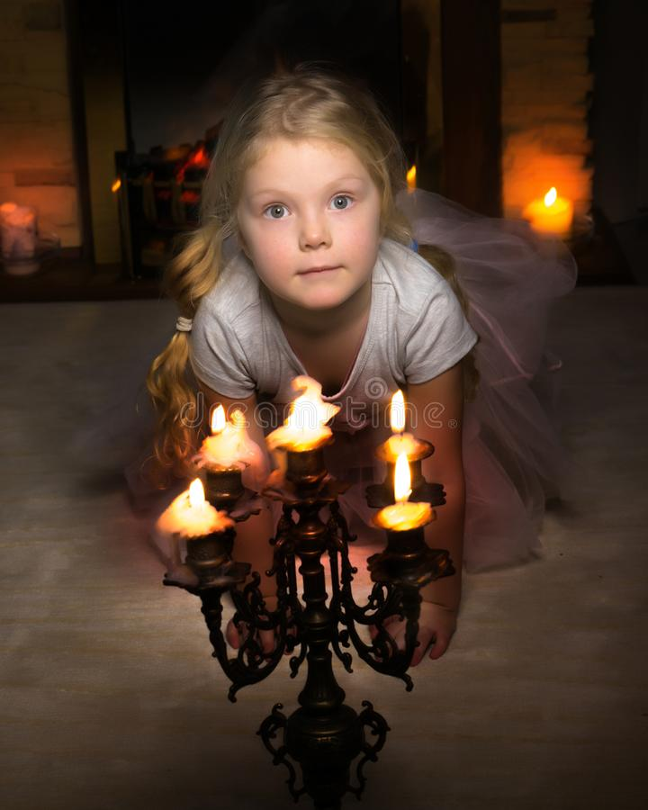 Une petite fille dans une chambre noire par lueur d'une bougie photo stock