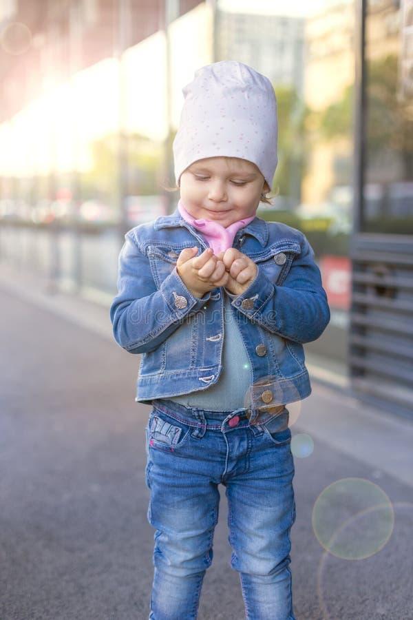 Une petite fille dans des jeans portent des expositions sur la rue photo libre de droits