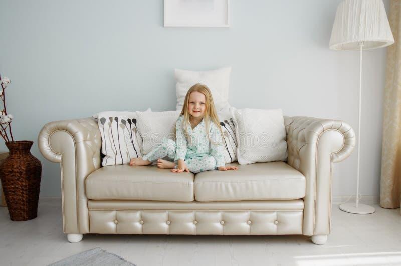 Une petite fille dans des pyjamas s'assied sur un sofa en cuir images libres de droits