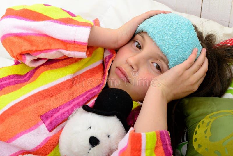 Une petite fille dans son lit a un mal de tête photographie stock libre de droits