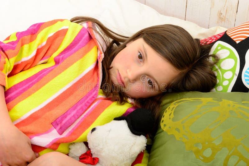 Une petite fille dans son lit a un mal de ventre images stock