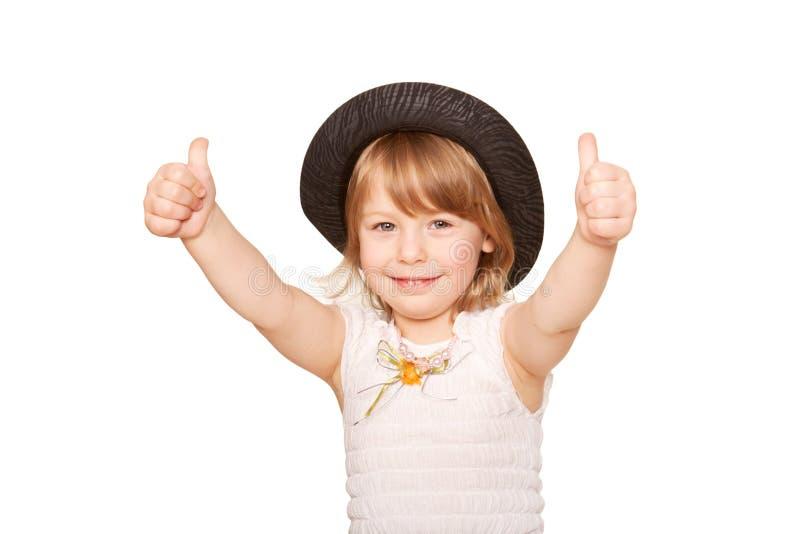 Une petite fille dans un chapeau noir montrant des pouces vers le haut. photo stock