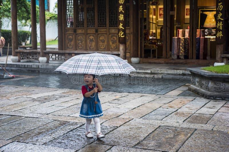 Une petite fille dans un chemisier rouge, une jupe bleue et des bas blancs avec un parapluie de plaid dans le secteur scénique photographie stock libre de droits