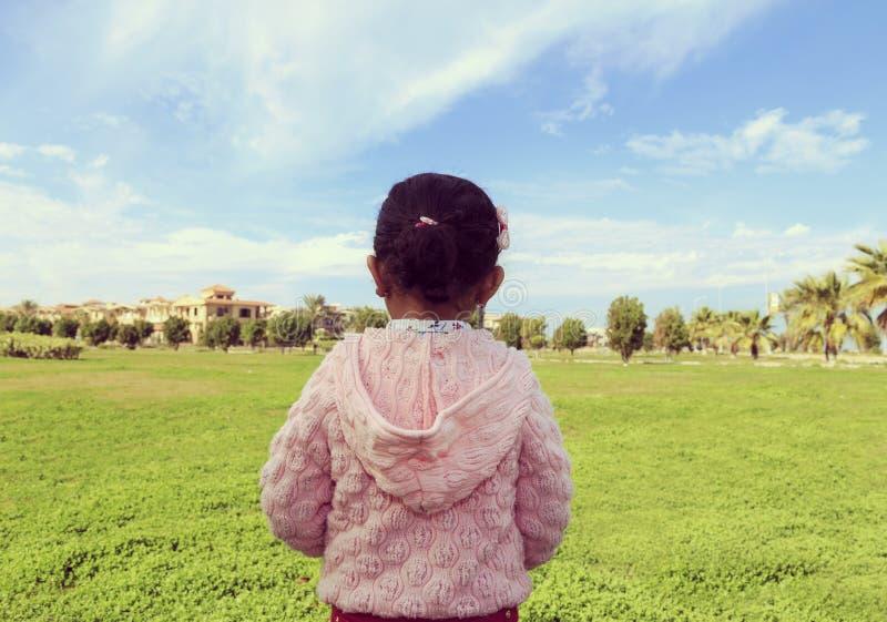 Une petite fille dans un jardin avec le ciel bleu images stock