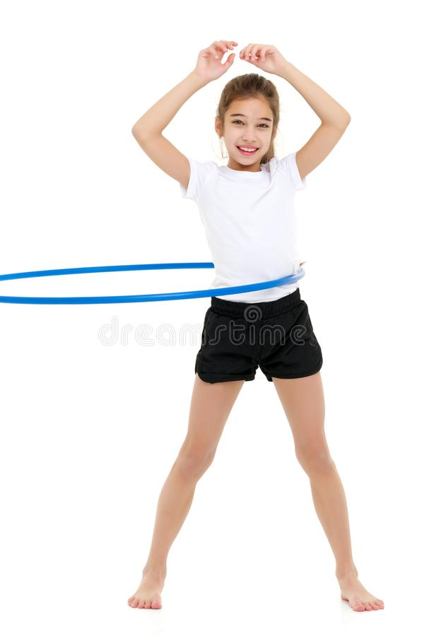 Une petite fille dans un T-shirt blanc exécute des exercices avec un cercle photos stock