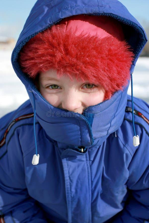 une petite fille dans une veste bleue d'hiver et dans le capot dans le jour d'hiver givré Vue supérieure photos stock