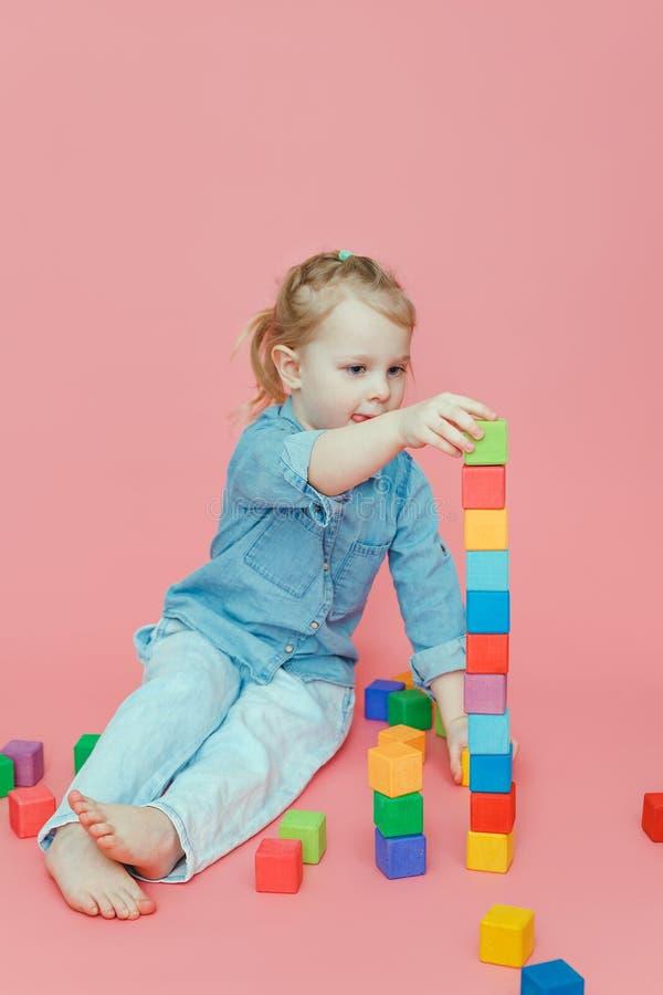 Une petite fille de charme dans des vêtements de denim sur un fond rose construit une tour photo stock
