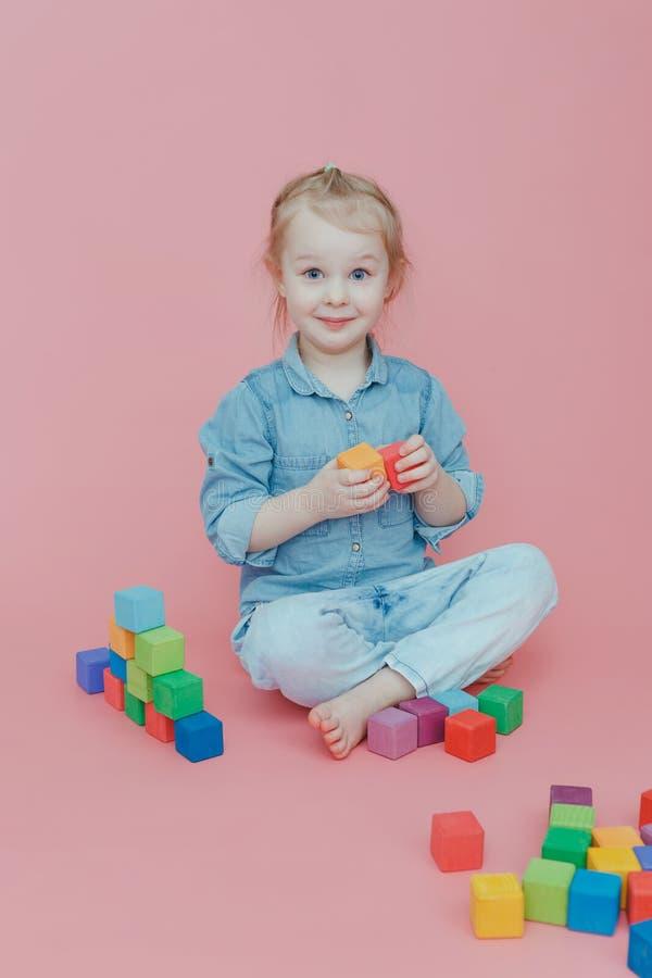 Une petite fille de charme dans des vêtements de denim sur un fond rose joue avec les cubes colorés en bois images stock