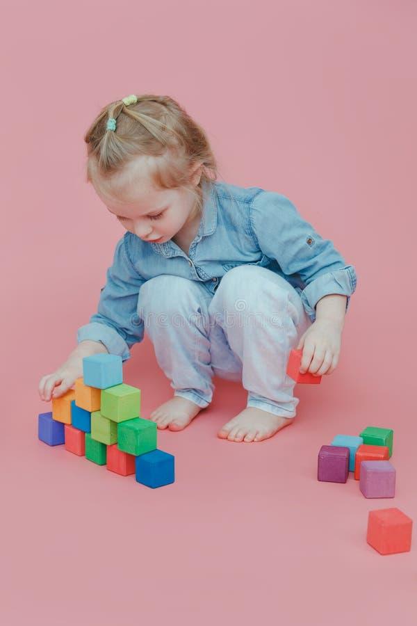 Une petite fille de charme dans des vêtements de denim sur un fond rose joue avec les cubes colorés en bois image stock