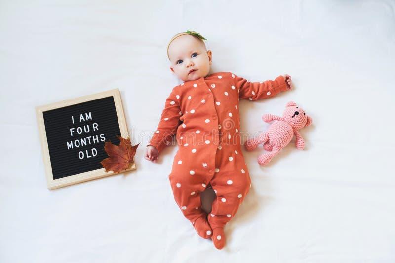 Une petite fille de quatre mois allongée sur un fond blanc avec carton à lettre et ours en peluche Composition de la couche plate photos stock