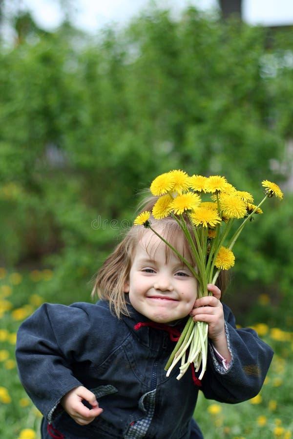 Une petite fille de sourire avec un bouquet des pissenlits jaunes images stock