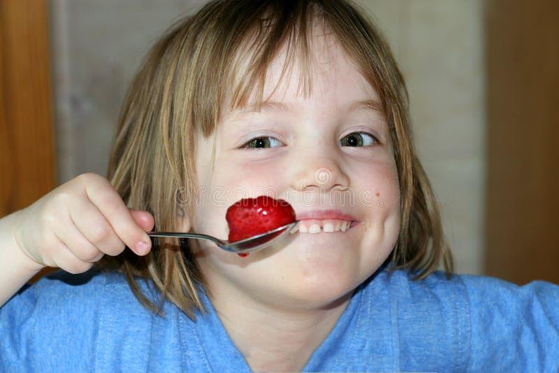Une petite fille de sourire mange des fraises par la cuillère photo libre de droits