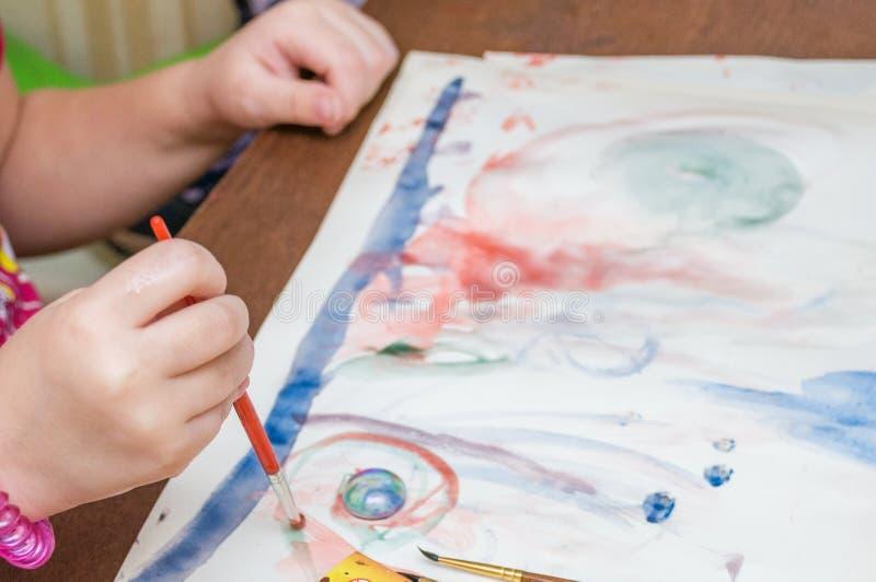 Une petite fille dessine l'image avec des peintures et une brosse photo libre de droits