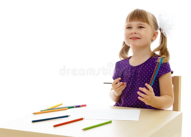 Une petite fille dessine ? la table images stock
