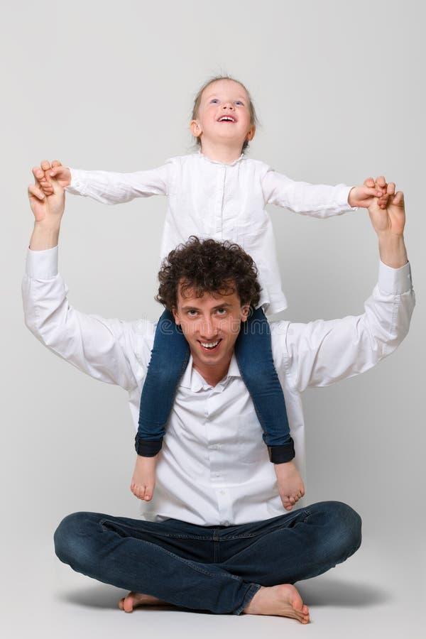 Une petite fille douce s'asseyant sur des épaules de son père L'homme repose les jambes croisées Ils rient joyeux Le concept d'he photographie stock libre de droits