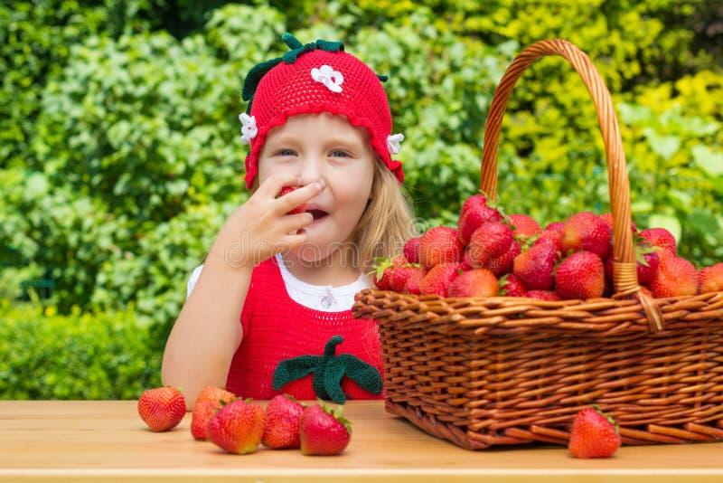 Une petite fille drôle 4 années avec un panier des fraises image libre de droits