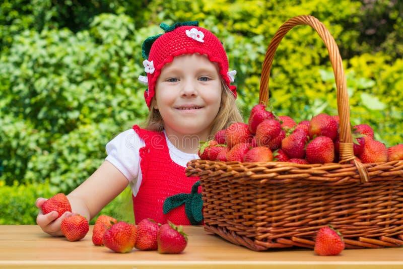Une petite fille drôle 4 années avec un panier des fraises photographie stock