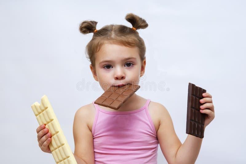 Une petite fille drôle surprenante tenant du chocolat et regardant images libres de droits