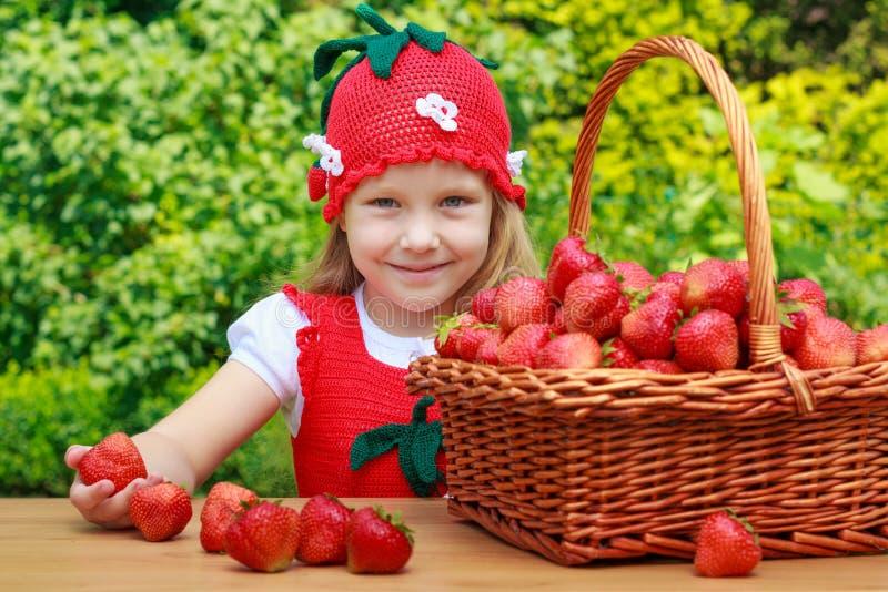 Une petite fille drôle 4 années avec un panier des fraises photographie stock libre de droits