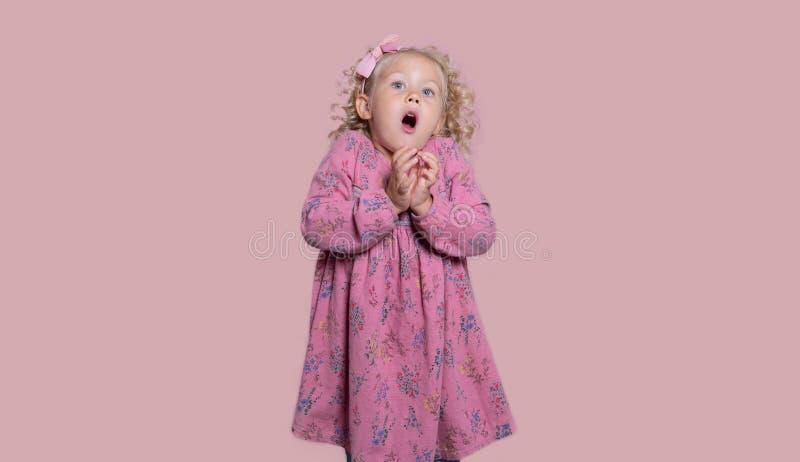 Une petite fille a effrayé de quelque chose, d'isolement au-dessus du blanc image stock