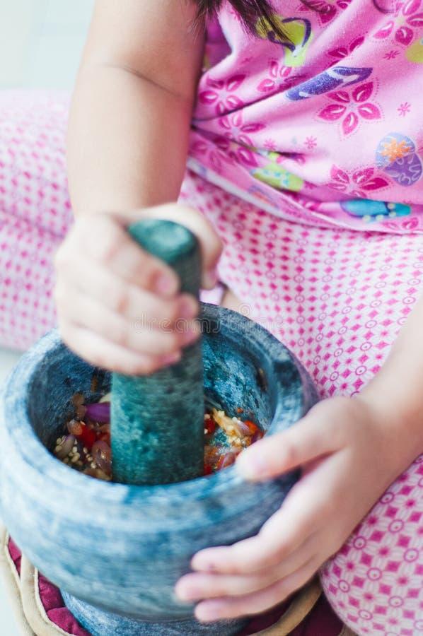 Une petite fille emploie le batu de mortier et de pilon ou de lesung dans le Malais photographie stock libre de droits