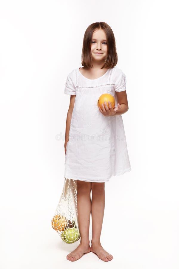 Une petite fille en robe blanche, tenant un sac de fruits d'une main et une orange de l'autre images stock