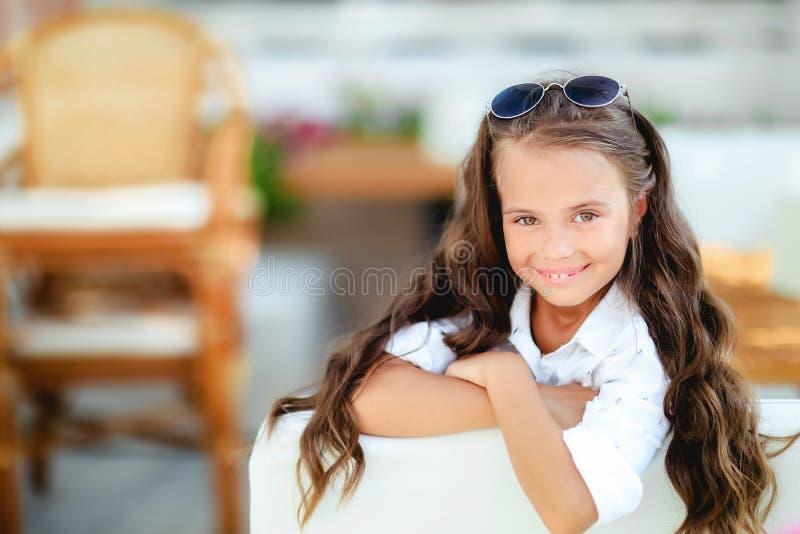 Une petite fille en verres ? la mode sur le fond de terrasse avec de longs sourires de cheveux boucl?s devant la cam?ra image libre de droits