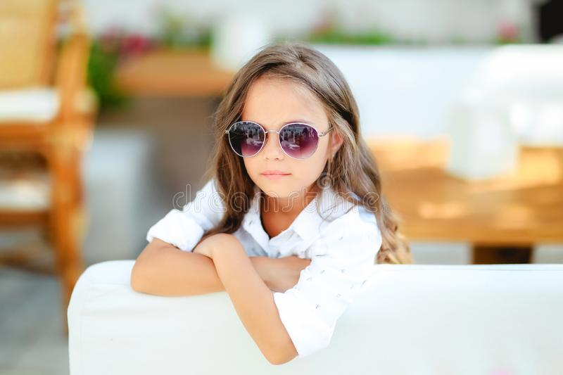 Une petite fille en verres ? la mode sur le fond de terrasse avec de longs sourires de cheveux boucl?s devant la cam?ra images libres de droits