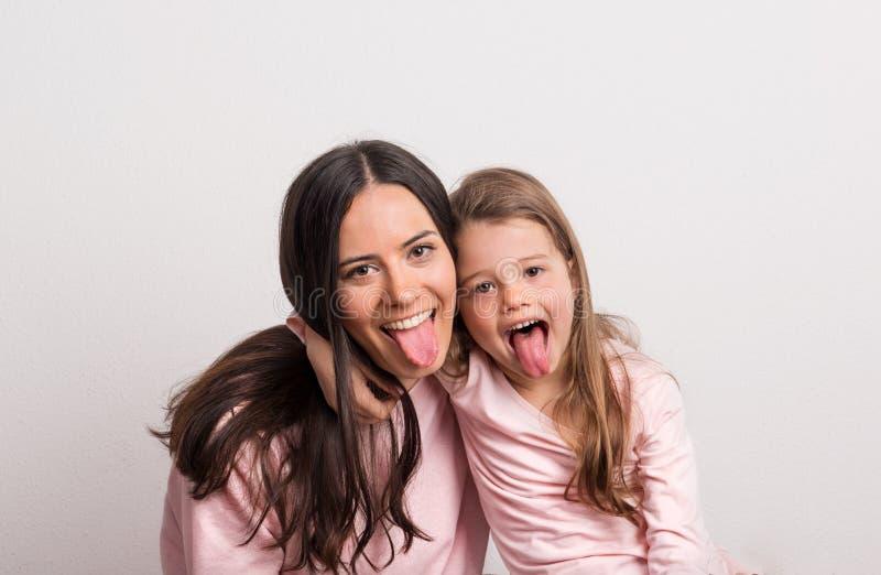 Une petite fille et sa mère collant des langues dans un studio image libre de droits