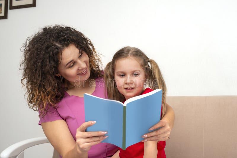 Une petite fille et sa mère passant le temps ensemble Ils s'asseyent sur le divan et lisent un livre image stock