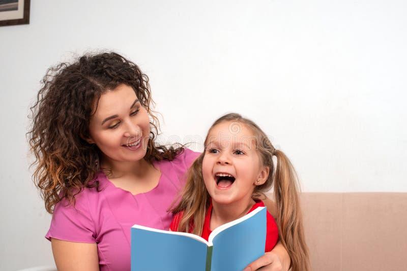 Une petite fille et sa mère passant le temps ensemble Ils s'asseyent sur le divan et lisent un livre photographie stock